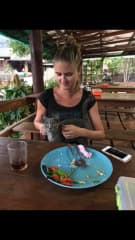 Claire and friendly cat at a restaurant in Thailand