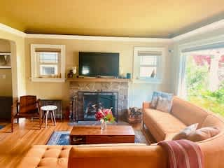 Living room with a wood burning fireplace and large screen TV.