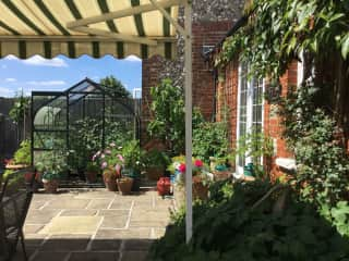 Part of house, patio and small greenhouse