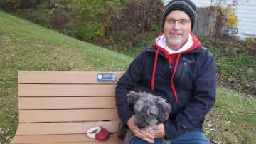 Roger with our little doggy on a bench installed by one of our son's eagle scout friends