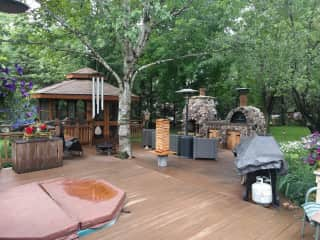 Our inviting deck with a pizza oven, fireplace, hot tub, and the gazebo, great for relaxing and reading.