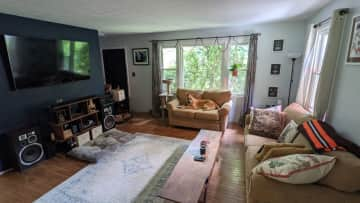 Living room with large TV and windows.