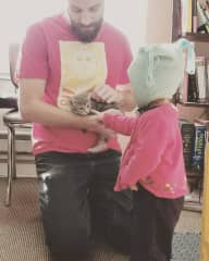 Ben holding a foster kitten with a toddler