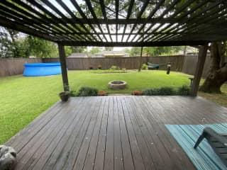 Huge backyard with vegetable garden and patio.