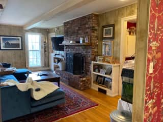 Downstairs den with fireplace, powder room, and laundry. Connects to kitchen and breakfast area.