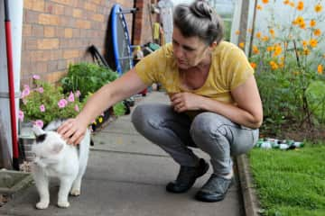 Margaret with George, a daily visitor to our garden during the past ten years.  George calls by to say hello and get some treats.  George's owner was 100 when she died a few years ago and George missed her greatly.  This lady's son now looks after George