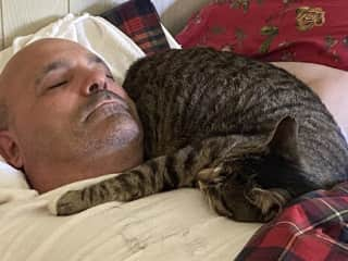 Tiger was a rescue cat and wasn't very friendly when we first got him. No our Tiger loves to sleep on Bruce!
