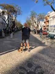 Jim takes sweet Ryia for a walk to town on our petsit in Portugal.