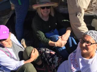 I am the person with hat and sunglasses, riding in the back of a farmer's truck after a hike and farm tour.