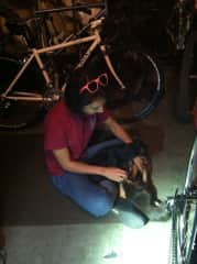 Julie with Nugget, working on bikes.