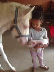 Our daughter Jairah with our horse White Star and our piglet