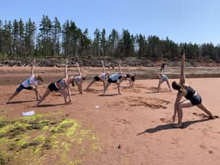 Me teaching a yoga class to youth from my church on the beach