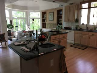 Kitchen with induction stove, family room and eat-in kitchen area.