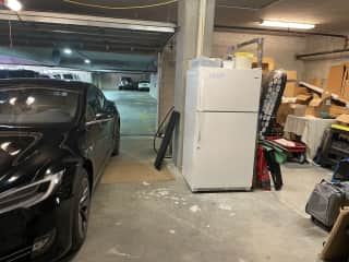"""Private garage with extra fridge looking in to """"public"""" garage.  Garage door is normally lowered for privacy and security.   Plenty of room for your bikes if you bring them."""