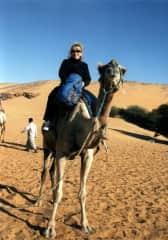 Riding a camel in the Sahara Desert