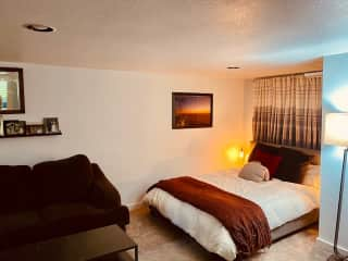 The lower floor queen bed and seating area with a comfortable sectional and a flat-screen TV.