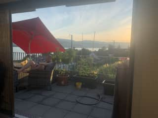 View from north-facing terrace, stocked with plants and comfortable seating for outdoor dining & relaxing