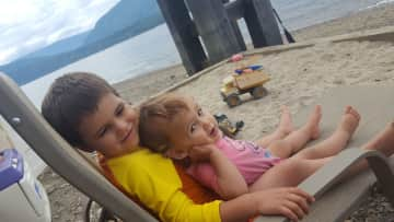 Theo snuggling with Daphne, enjoying beach time in Canada
