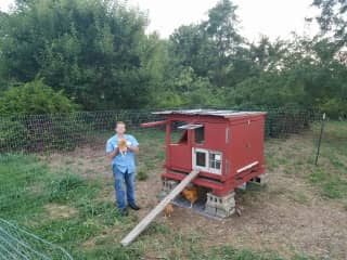 My husband with our first chickens and the house he built for them at our farm.
