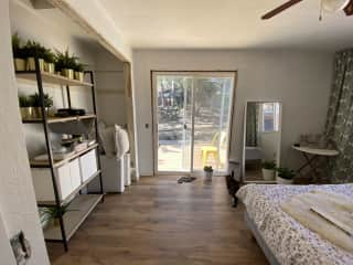 An older photo of the guest room! It's a work in progress but this shows the size and the doors to the back yard and deck. There is now a desk area, side tables, and more plants.