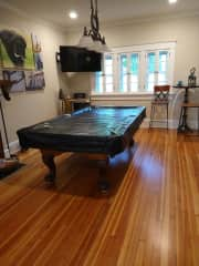 The entertaining room features a full size pool table, and a hard-tip dart board.