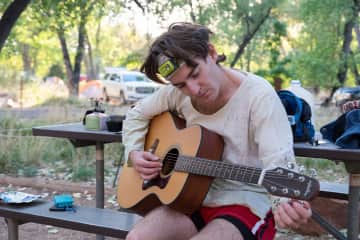 Tuning up the guitar at a campground.