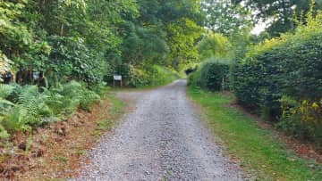 The cottage is on the right and the parking area is on the left.