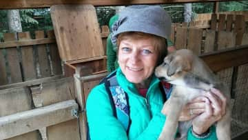 Sheryl with dog sled pup in Alaska