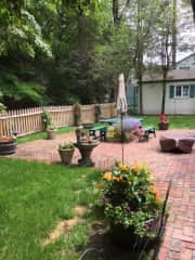 patio at the back with fenced in garden covering a part of the property. Separate garage in the background.