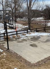 The half-court concrete height-adjustable basketball hoop is next to the neighborhood's circular path and open areas that serve as wildlife preserves.