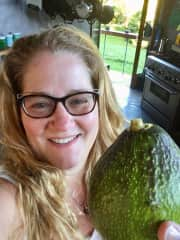 Laura with a huge avocado from the orchard in Hawaii.