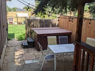 Side yard with hot tub, grill and outdoor dining table. Chicken coop and run are visible in the background.