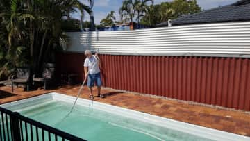 Bob is vacuuming the pool during our housesit in the Gold Coast.