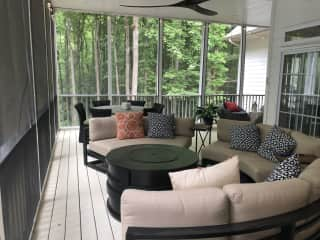 Large screened in porch with 2 seating areas, fire table and dining table for 6.
