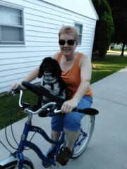 Carol likes to ride bike with her dog Slippers