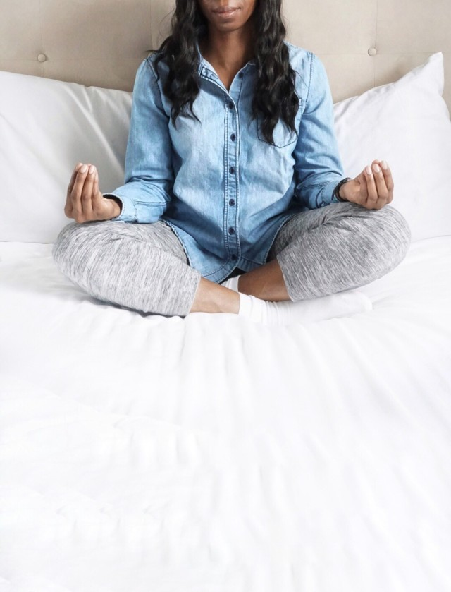 Woman sitting with legs crossed casually dressed doing meditation on a bed with space for copy