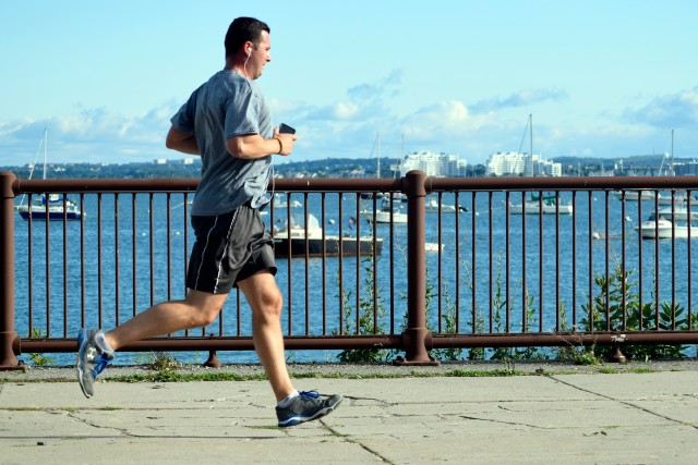 Man jogging along the Boston coastline listening to music from his phone with boats in a harbor in the background on a sunny summer day