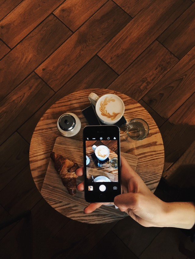 Woman taking photo of coffee on mobile device