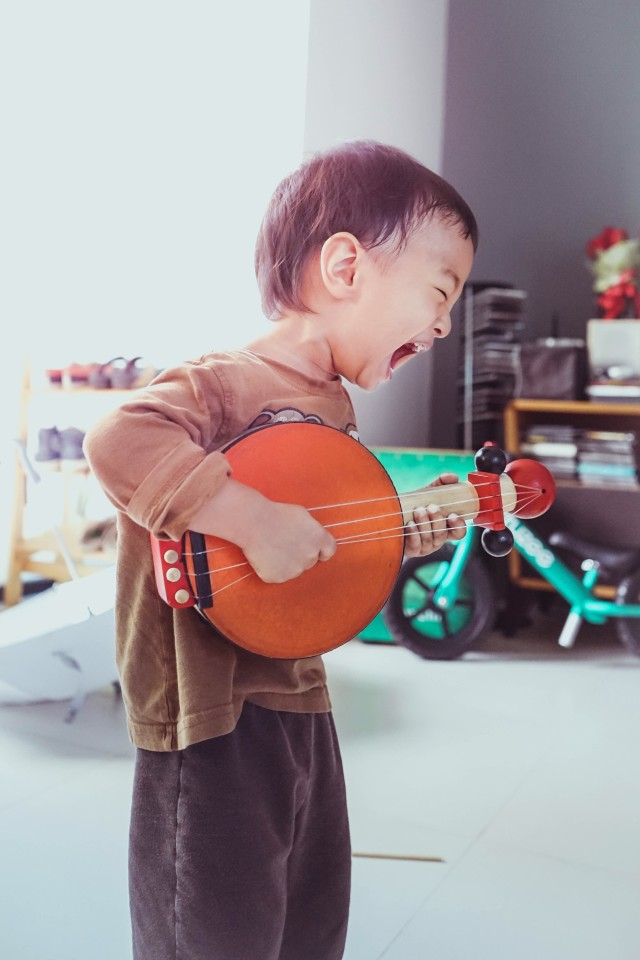 A boy is playing toy guitar.