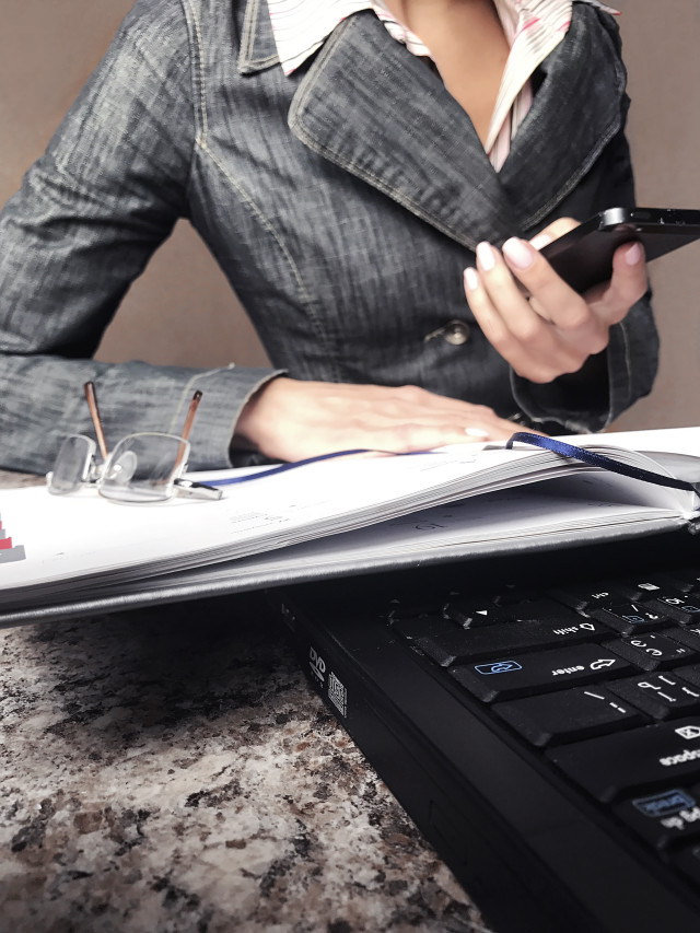 Young business woman working at laptop using her planner and mobile phone