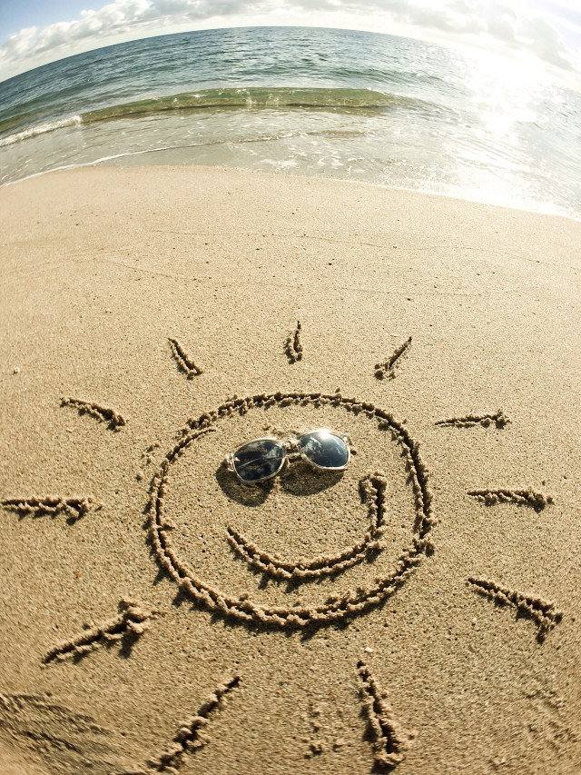 Sun drawn on the sand with sunglasses on 😎