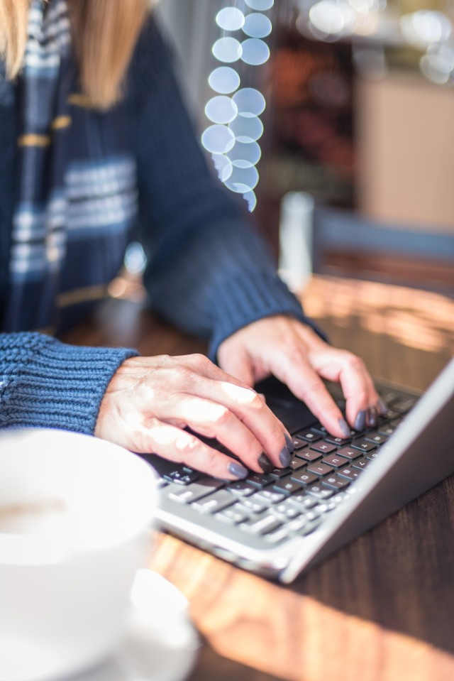 Woman in sweater typing on laptop keyboard at coffee shop in winter