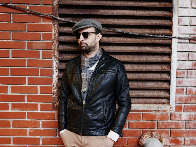 An urban portrait of a young man with a beard. He's wearing a bright sweater, a scarf, a leather jacket and a hat. He's stading in front of a brick wall and wearing sunglasses.