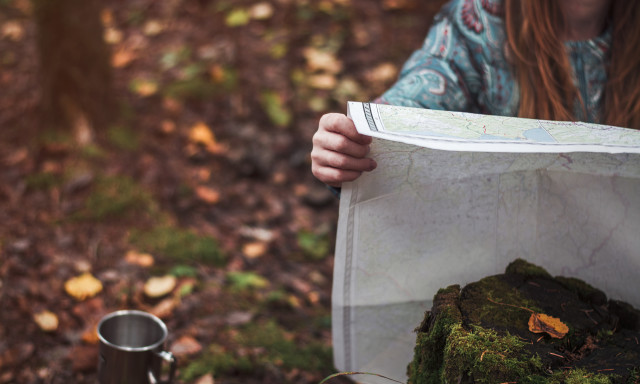 Female traveler with a map in the fall forest.