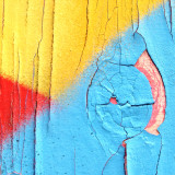Red, yellow and blue decaying paint on wood.