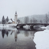 Church on the Bridge in the winter. Winter Fairytale at Bohinj Lake in Slovenia. Mystical landscape on a winter day with heavy snow. Cottages reflection in the Snow.