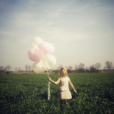 Pretty little girl with balloons in a flemish landscape near Bruges