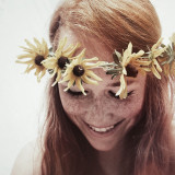 Girl with flower crown laughing.