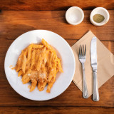 Pasta plate in rustic table with salt and pepper