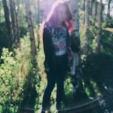 Blurry, artistic photo with lens flares, of a stylish teen girl.